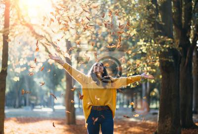 Posters Casual femme joyeuse s'amuser jetant des feuilles en automne au parc de la ville.
