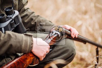 Posters chasseur de chargement de fusil dans une forêt d'hiver. Bushcraft, chasse et concept de peuple