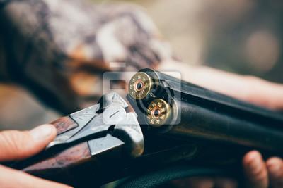 Posters Chasseur mâle dans la forêt d'automne. Un homme tenant une arme à feu.