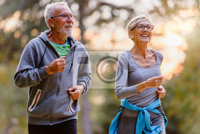 Posters Cheerful active senior couple jogging in the park. Exercise together to stop aging.