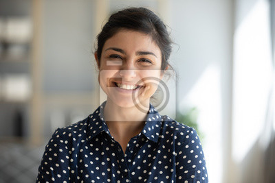 Posters Cheerful indian girl standing at home office looking at camera