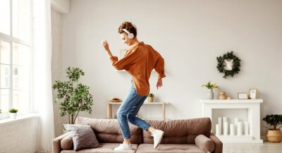 Posters Cheerful woman listening to music and dancing on soft couch at home in day off.