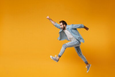 Posters Cheerful young bearded man in casual blue shirt posing isolated on yellow orange background studio portrait. People lifestyle concept. Mock up copy space. Jumping with outstretched hand like Superman.