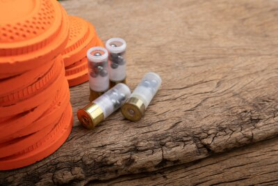 Posters Clay pigeons and shotgun bullets on wooden background , Clay target shooting game , Can be used as a background