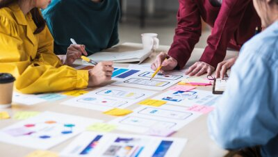 Posters Close up ux developer and ui designer brainstorming about mobile app interface wireframe design on table with customer breif and color code at modern office.Creative digital development agency.