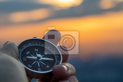 Posters compass in hand with sunset sky on the background