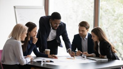 Posters Confident african American male boss work cooperate with diverse team at office briefing, focused biracial businessman head meeting, collaborate discuss business ideas with colleagues at meeting