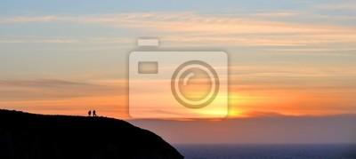 coucher de soleil et personne en haut d'Une montagne