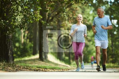 Posters Couple âgé actif et en bonne santé en cours d'exécution dans un environnement naturel le matin d'été