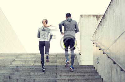 Couple courant en haut des escaliers de la ville