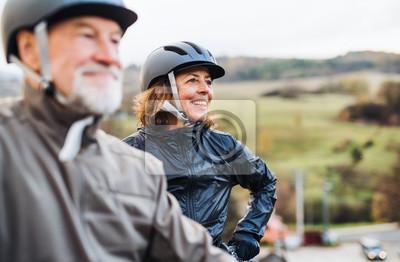 Posters Couple de personnes âgées actives avec des vélos électriques, debout à l'extérieur sur une route dans la nature.