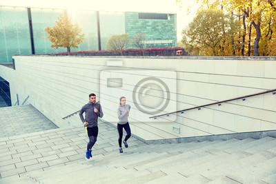 couple heureux en cours d'exécution à l'étage dans les escaliers de la ville
