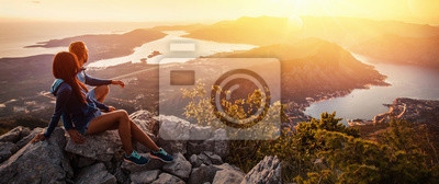 Posters Couple heureux en regardant le coucher de soleil dans les montagnes