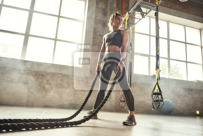 Posters CrossFit training. Young athletic woman with perfect body doing crossfit exercises with a rope in the gym.
