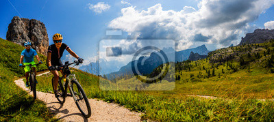 Posters Cycling woman and man riding on bikes in Dolomites mountains landscape. Couple cycling MTB enduro trail track. Outdoor sport activity.
