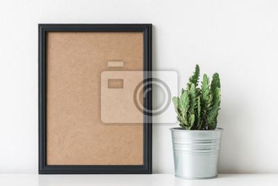 Décoration de la chambre moderne. Plante de cactus en pot de fleur blanche. Maquette avec un cadre noir.