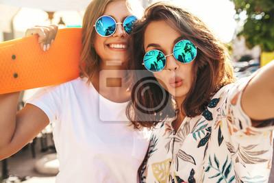 Posters Deux modèles de femmes jeune et élégante hippie brune et blonde femmes en vêtements d'été hipster prenant des photos de selfie pour les médias sociaux sur smartphone sur le fond de la rue. Avec des pl
