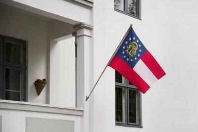 Posters Drapeau d'État agitant une maison sur un poteau sur la porte d'entrée d'un bâtiment.