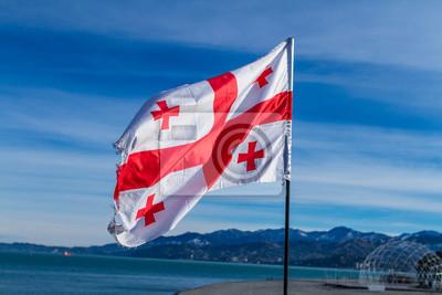 Posters Drapeau géorgien dans le vent sur fond de ciel bleu et clair