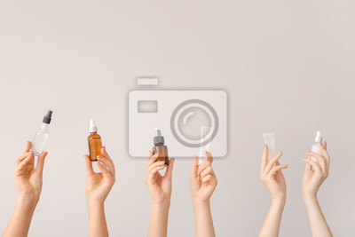 Posters Female hands with different cosmetic products in bottles on grey background