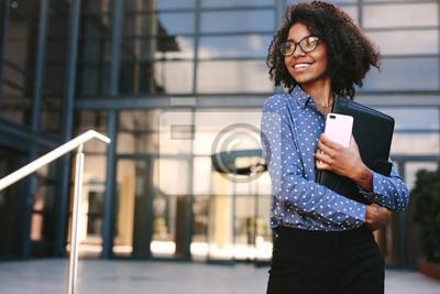Posters Femme d'affaires heureux debout devant un immeuble de bureaux