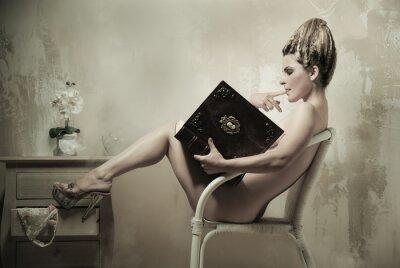 Posters Femme nue assise dans un fauteuil en lisant un livre à l'intérieur