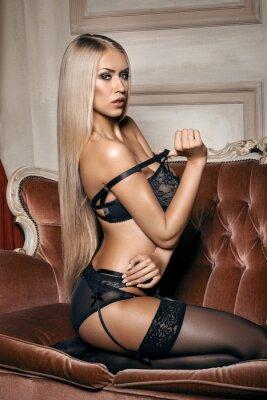 Posters femme sexy en lingerie noire séduisante assis sur un canapé en bas