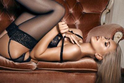 Posters femme sexy en lingerie noire séduisante couchée sur un canapé dans les bas