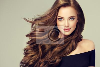 Posters Fille brune aux longs et brillants cheveux ondulés. Beau modèle avec une coiffure bouclée.