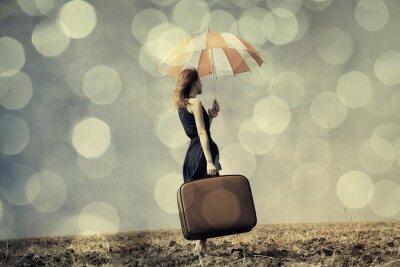 Posters Fille rousse avec un parasol et valise au champ venteux