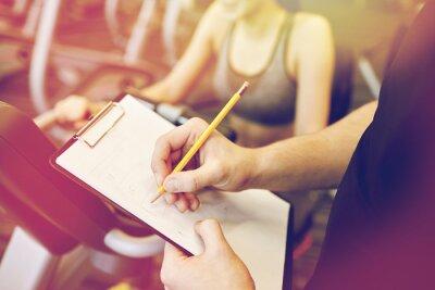 Fin, haut, formateur, mains, presse-papiers, gymnase