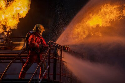 Posters Firefighter in the training with fire hose nozzle spraying high pressure water to fire, Firefighter wearing a fire suit for safety under the danger case