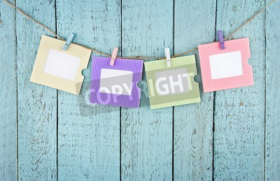 Posters Four empty colorful photo frames or notes paper hanging with clothespins on wooden blue vintage shabby chic background