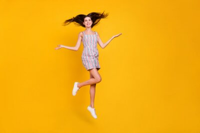 Posters Full length body size woman smiling jumping high happy throwing hair cheerful isolated vivid yellow color background