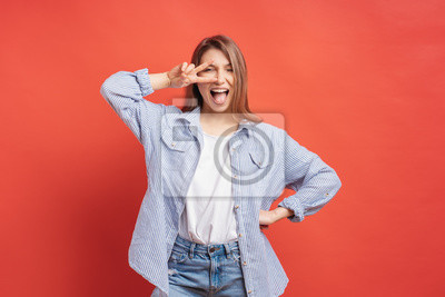 Posters Funny, carefree girl having fun isolated on a red background with open mouth