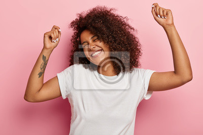 Posters Funny joyous woman raises arms and dances carefree, feels pleasure and amused, laughs happily, eyes closed from satisfaction, moves along with music, has tattoo dressed in casual wear isolated on pink