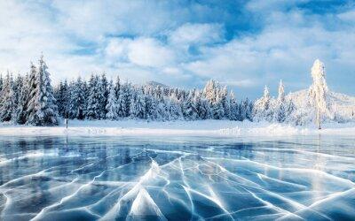 Posters Glace bleue et fissures à la surface de la glace. Lac gelé sous un ciel bleu en hiver. Les collines de pins. Hiver. Carpates, Ukraine, Europe.