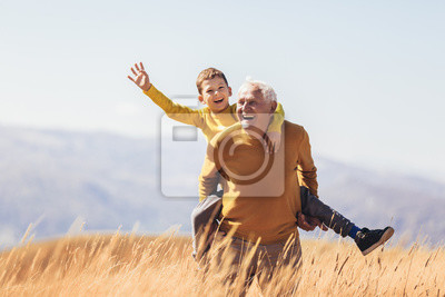 Posters Grandson piggyback with his grandfather in autumn.