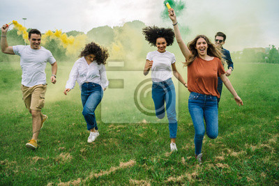 Posters Group of five friends runs in a park with two smoke bombs at the park - Millennials have fun together in the summer at sunset