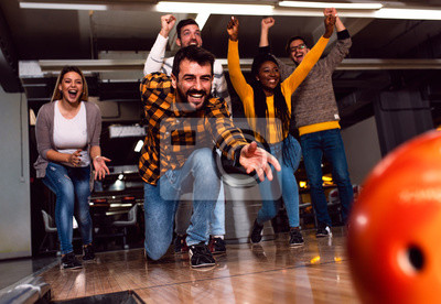 Posters Group of friends enjoying time together laughing and cheering while bowling at club.