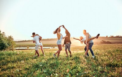 Posters group of happy young people dancing on the field on beautiful summer sunset