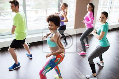 groupe de gens souriants danser dans une salle de sport ou en studio
