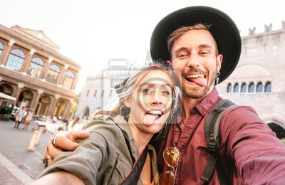 Posters Happy boyfriend and girlfriend in love having genuine fun taking selfie at old town tour - Wanderlust life style travel vacation concept with tourist couple on city sightseeing - Bright warm filter