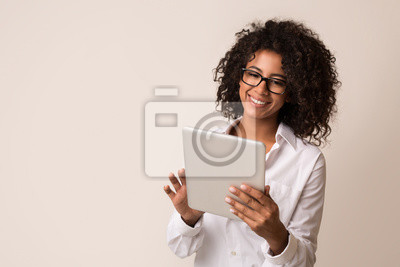 Posters Happy businesswoman using tablet over light background