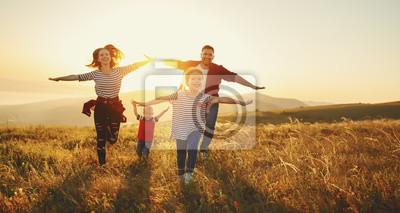 Posters Happy family: mère, père, fils et fille au coucher du soleil
