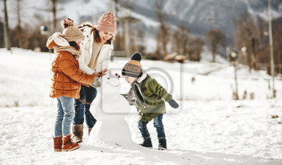 Posters happy family mother and children having fun on winter walk