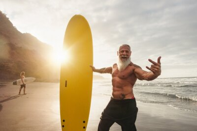 Posters Happy fit senior having fun surfing at sunset time - Sporty bearded man training with surfboard on the beach - Elderly healthy people lifestyle and extreme sport concept