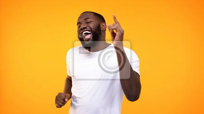 Posters Happy relaxed black man dancing against yellow background, having fun on party