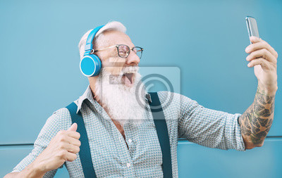 Posters Happy senior man taking selfie while listening music with headphones - Hipster mature male having fun using mobile smartphone playlist apps - technology and elderly lifestyle people concept