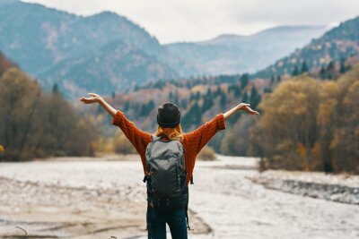 Posters happy woman hiker with a backpack on the river bank look into the mountains and autumn forest nature